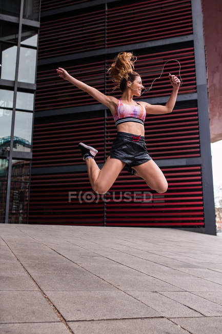 Excited muscular fit woman in sportswear jumping happily with hands apart on paved street — Stock Photo