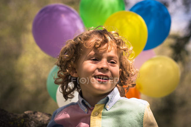 Portrait of preschooler boy with colorful balloons — Stock Photo