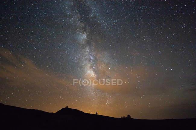 Céu estrelado com infinita galáxia acima do terreno escuro — Fotografia de Stock