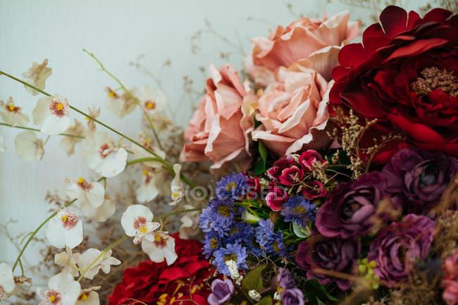 Elegante buquê de rosas frescas vistosas e flores silvestres com flores secas e ervas — Fotografia de Stock