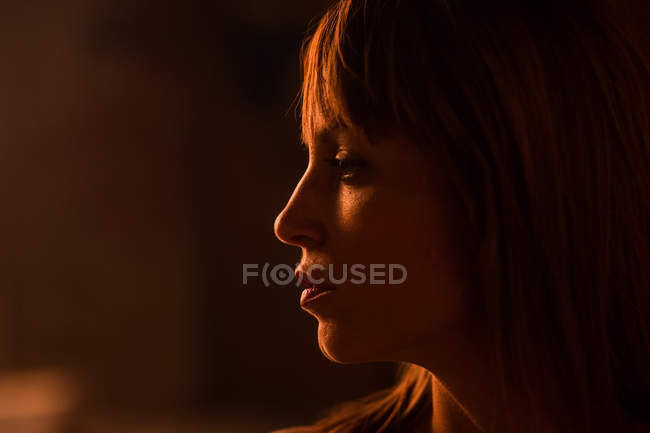 Emotionless young woman face with bangs standing in soft gold light of sunset and looking away — Stock Photo