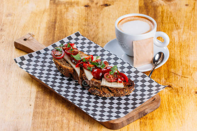 Brown bread sandwich with cheese and tomatoes and cup of cappuccino on wooden table — Stock Photo