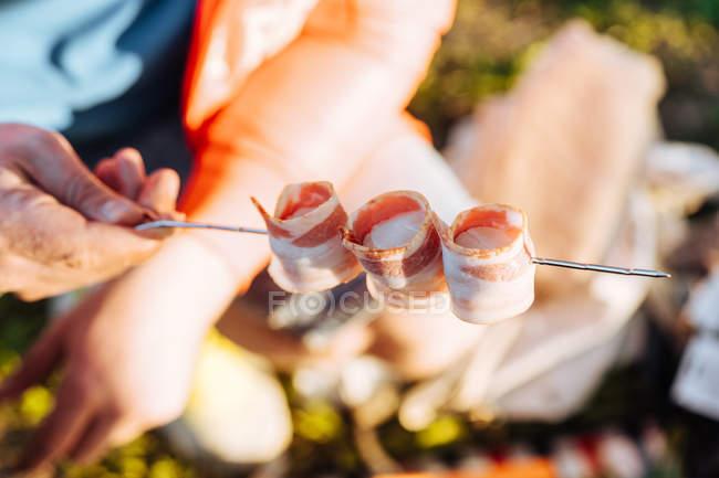 Mano umana che tiene pancetta piegata strisce sullo spiedo in metallo per pasto barbecue — Foto stock