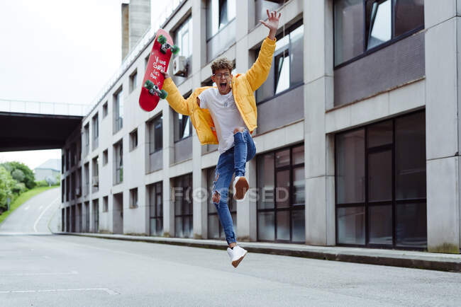 Happy and excited teenager jumping with skateboard — Stock Photo
