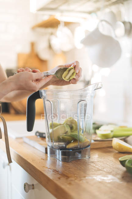 Female hands putting kiwi fruits in blender bowl for green smoothie — Stock Photo