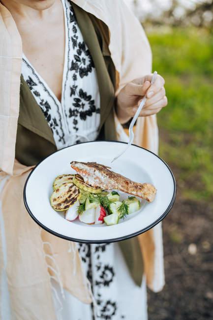Женщина держит тарелку свежих овощей с филе лосося гриль и цуккини на пикнике — стоковое фото