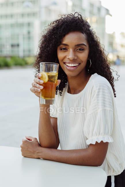 Mulher afro-americana encantadora segurando vidro de bebida no café ao ar livre — Fotografia de Stock