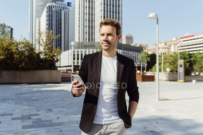 Elegant man holding smartphone while standing on street of modern city — Stock Photo