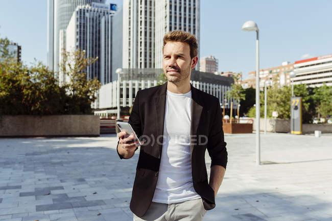 Homme élégant tenant smartphone tout en se tenant sur la rue de la ville moderne — Photo de stock