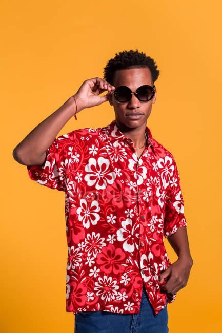Stylish cheerful man in beach shirt and sunglasses standing on orange background — Stock Photo