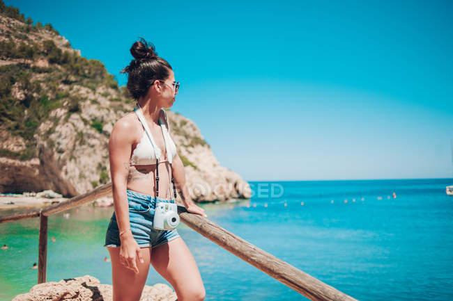 Chica joven en ropa de verano, apoyado en el pasamanos de madera en la playa - foto de stock