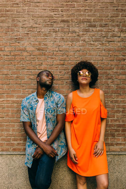 Attractive African American man and woman in stylish sunglasses leaning on brick wall on street — Stock Photo