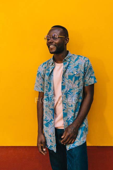 Junger afrikanisch-amerikanischer Mann lächelt, während er vor einer knallgelben Wand steht — Stockfoto