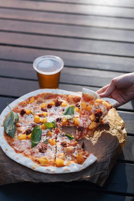Крупным планом женской руки с кусочком пиццы — стоковое фото