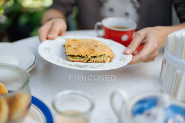 Female hands holding piece of pasty on plate on garden table — Stock Photo