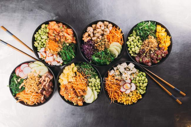 Керамічні миски різні страви азіатської кухні на чорній поверхні металу — стокове фото