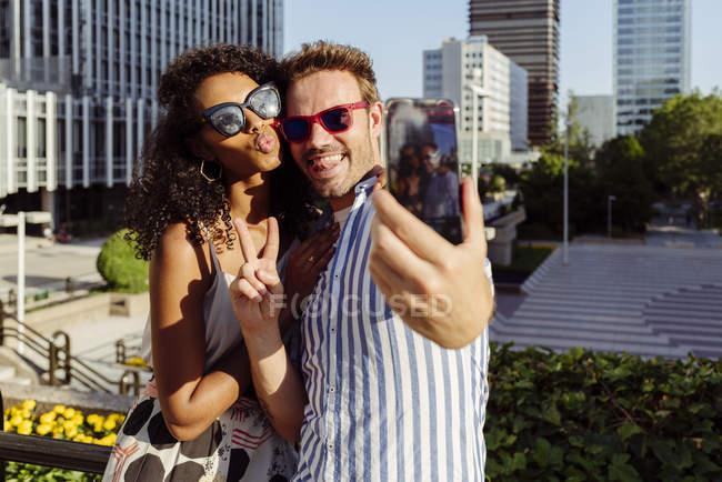 Веселая многорасовая пара позирует для селфи, стоя на фоне современного города — стоковое фото