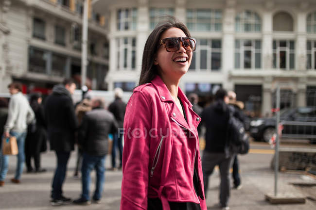 Stylish smiling woman in pink leather jacket on street — Stock Photo