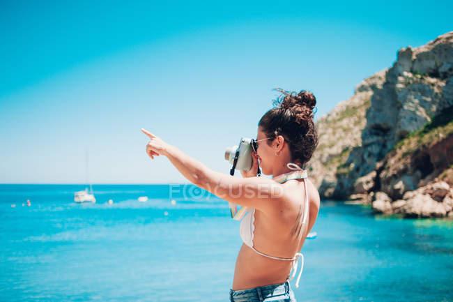 Молода жінка фотографують моря на пляжі і вказуючи рукою — стокове фото
