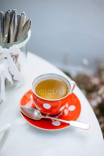 Tasse en céramique de pois de rouge de thé sur soucoupe sur la table de jardin — Photo de stock