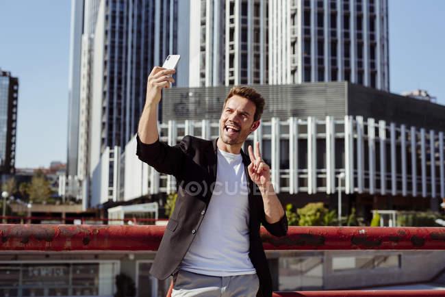 Веселый мужчина в повседневной одежде показывает победный жест и позирует для селфи в современном городе — стоковое фото