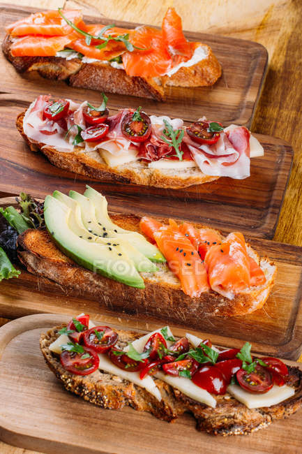 Assortment of nutritious different sandwiches on wooden board — Stock Photo