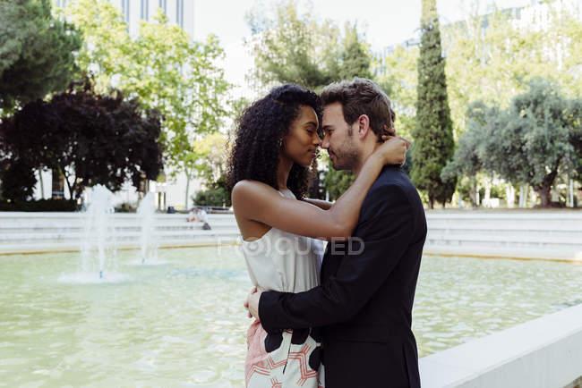 Elegante pareja multirracial abrazando cerca de la fuente en el parque de la ciudad - foto de stock