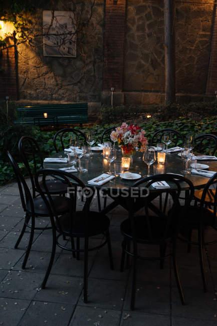 Tisch dekoriert mit Kerzen und Blumen, in der Nacht auf Hinterhof — Stockfoto
