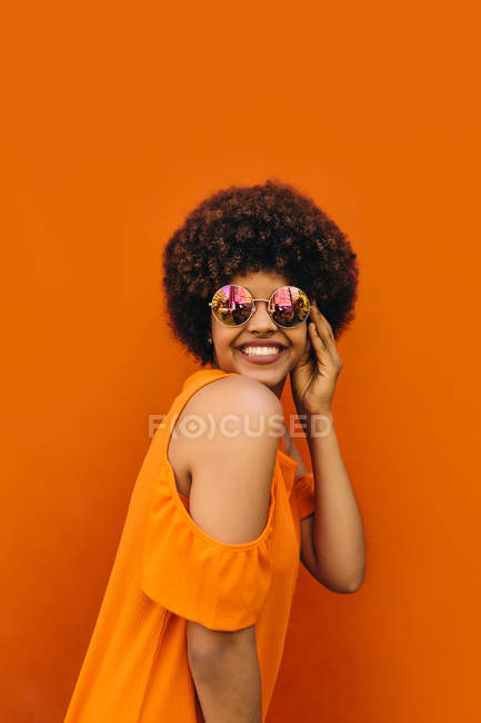 Black woman charmingly smiling and adjusting stylish sunglasses while standing on bright orange background — Stock Photo