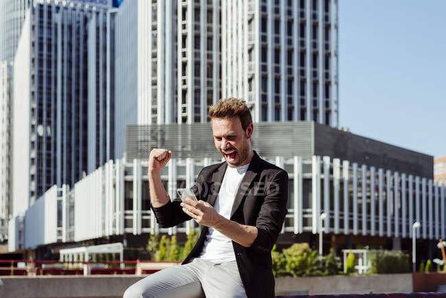 Excited man holding smartphone and rejoicing over victory while standing on street of modern city — Stock Photo