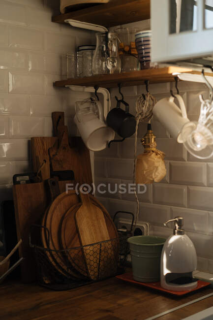 Interior of kitchen with white tiled walls and plenty of utensil and appliance composed on shelves and countertop — Stock Photo
