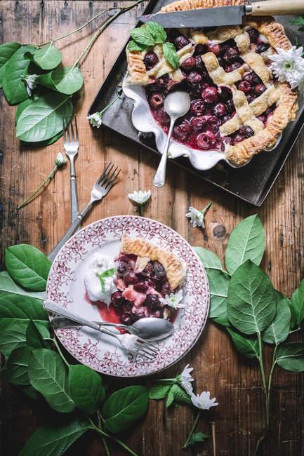 Piatto posare di torta di ciliegie al forno con crosta della grata, servito con gelato sulla tavola rustica con foglie verdi — Foto stock