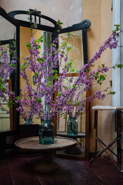 Beautiful freshly cut long twigs with green leaves and purple flowers standing in glass jar with water on round wooden table in old shabby room with mirrors — Stock Photo