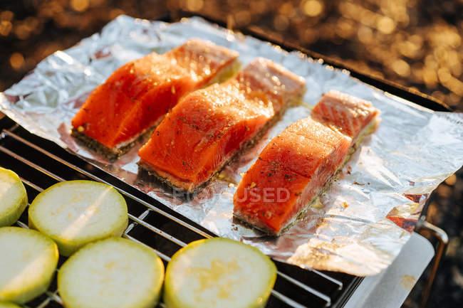 Кусочки лосося и цукини с фольгой на гриль сетки на открытом воздухе — стоковое фото