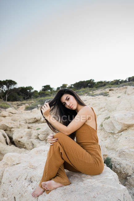 Stylish young woman sitting on rocks of shoreline, touching hair and looking in camera — Stock Photo
