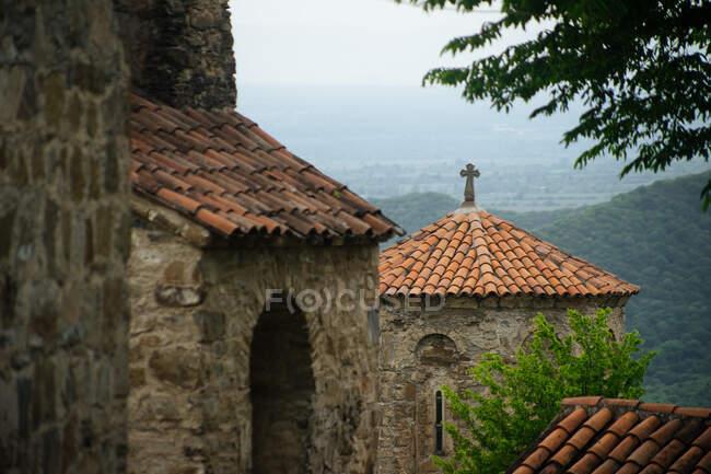 Bâtiment médiéval en pierre avec toit carrelé rouge et croix chrétienne sur le dessus debout à proximité vieil ensemble architectural dans le même style avec envahi par les arbres montagnes et les vallées sur fond — Photo de stock