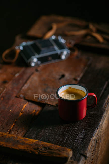 Enamel cup of coffee on rustic wooden surface with retro camera — Stock Photo