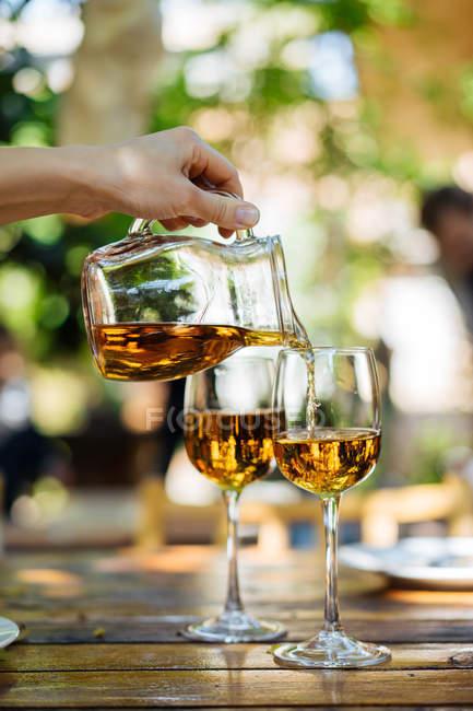 Человеческая рука наливает белое вино из стеклянного кувшина в бокалы на открытом воздухе — стоковое фото