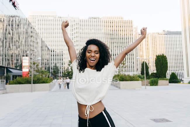 Взволнованная афроамериканка, стоящая на улице с поднятыми руками — стоковое фото