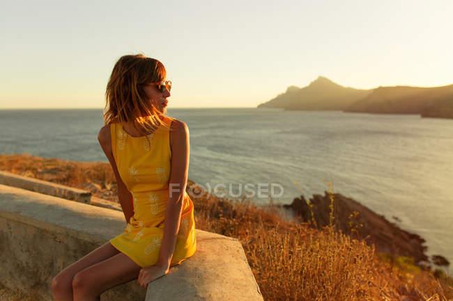 Frau in stilvollen kurzes Kleid und Sonnenbrillen sitzen auf der Terrasse mit Blick auf Meer bei Sonnenuntergang — Stockfoto