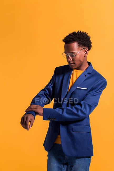 Stilvolle junger schwarzer Mann tragen moderne blaue Jacke mit Jeans und Pullover auf orangem Hintergrund stehend — Stockfoto