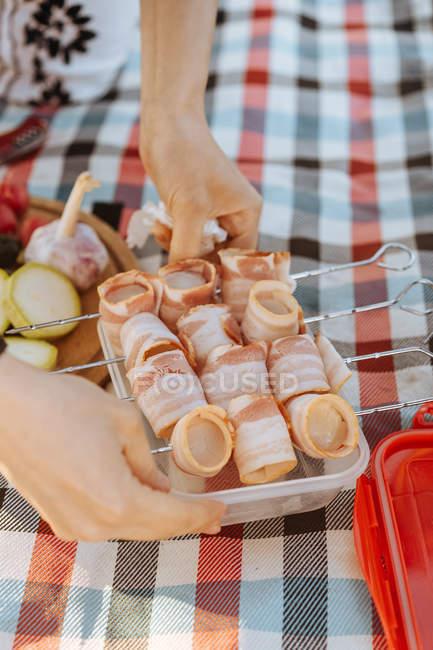 Primo piano delle mani umane che tengono spiedini di metallo con strisce di pancetta affumicata su piatto — Foto stock