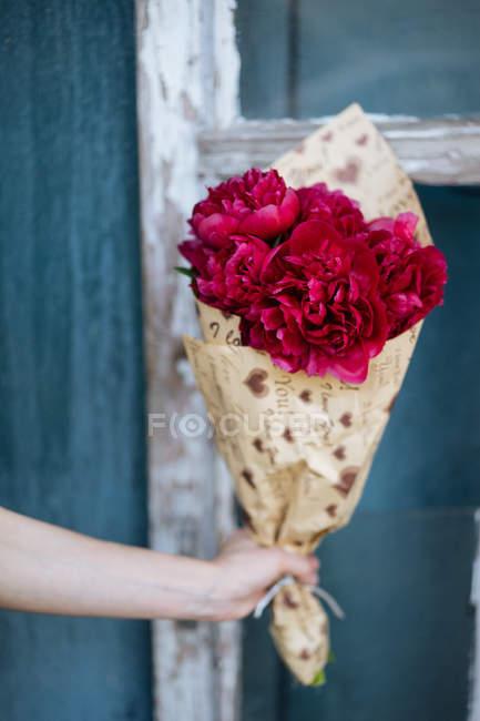 Людські руки, що тримає букет рожевий півонії в обгорткового паперу дерев'яними тлі — стокове фото