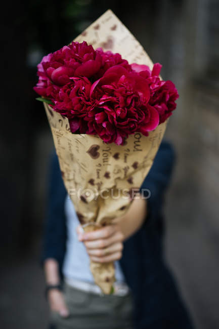 Woman holding bouquet of pink peonies in wrapping paper in front of face — Stock Photo
