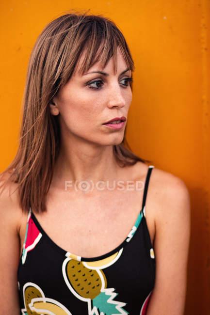 Jeune femme en maillot de bain à la recherche de suite contre conteneur orange — Photo de stock