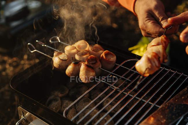 Самец руки подготовляя бекон и сосиски на шпажки гриль на сжигание угля в переносной гриль на открытом воздухе — стоковое фото