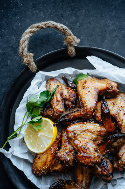 Close-up of baking dish of baked chicken wings in sesame and parsley with lemon — Stock Photo