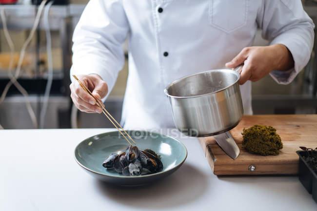 Chef que sirve plato de mariscos nórdicos con mejillones en el plato - foto de stock