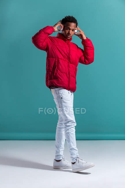 Trendy man in red puffy jacket and headphones standing on blue background — Stock Photo