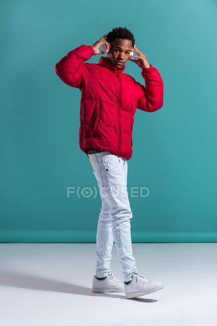 Модний чоловік у червоний куртка пухкі і навушники, стоячи на синьому фоні — стокове фото